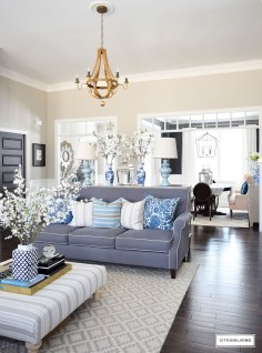open-concept-living-room-blue-and-white-spring-decor-tonic-living-pillows-striped-ottoman-faux-branches